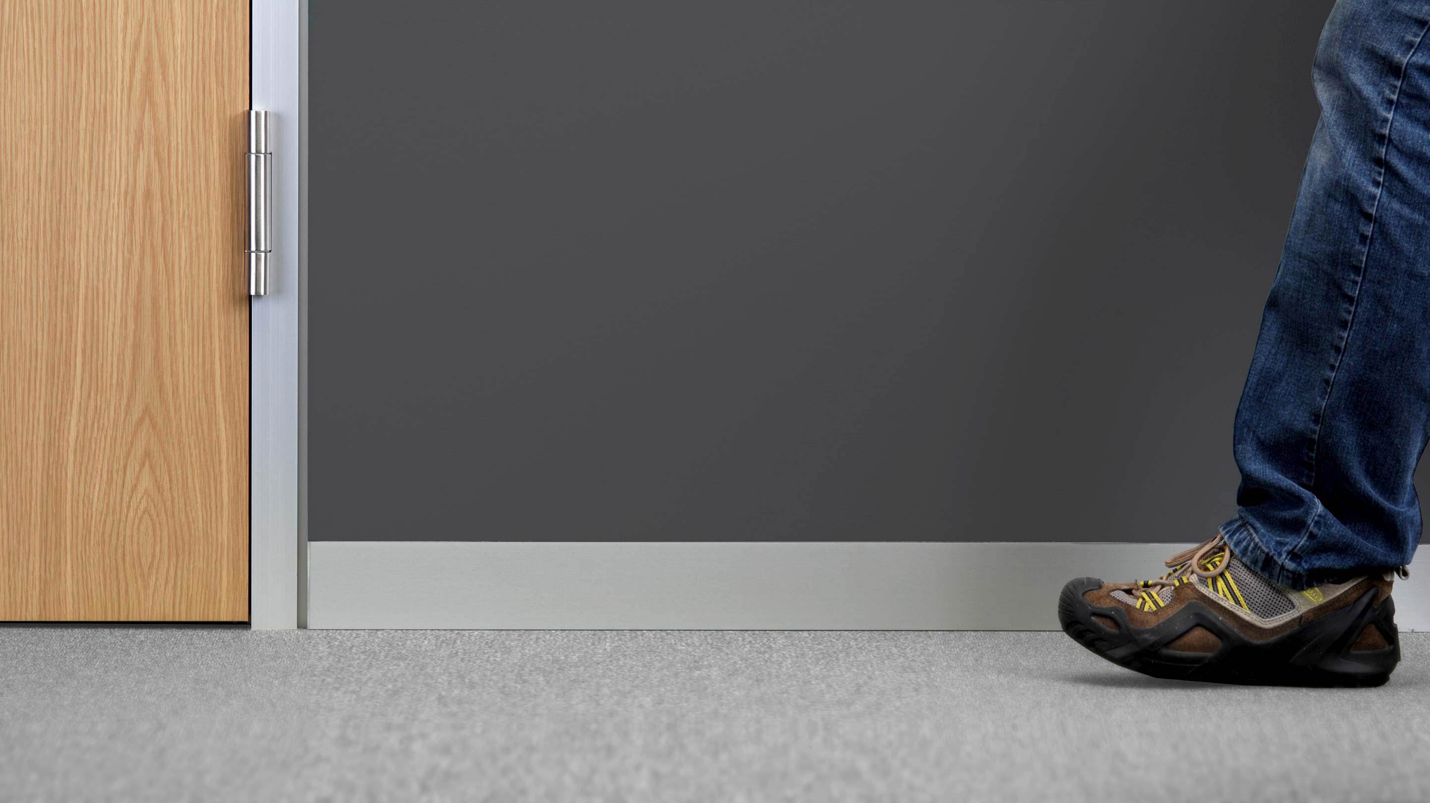 Sockelleiste mit Türblatt und Bein eines Menschen